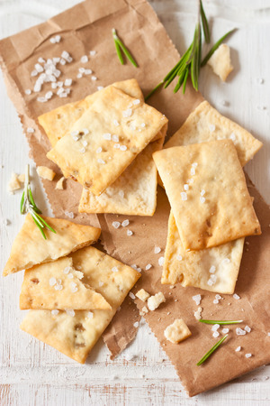 Homemade crackers with rosemary and sea salt for appetizer on an old cooking board.