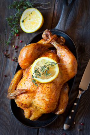 oven chicken: Whole roasted chicken with lemon and thyme on a pan. Rustic style.