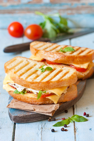 Grilled cheese sandwiches with chicken and tomatoes on a rustic wooden board. Stockfoto