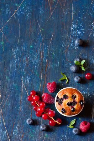 Sweet muffin surrounded by fresh berries with copy space for note or recipe.