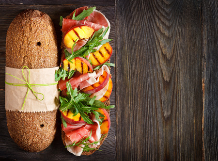Delicious ham sandwich with grilled peaches and arugula on an wooden background with place for text