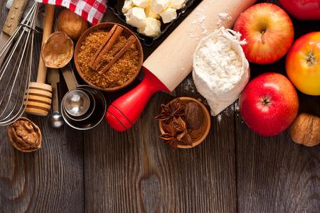 Ingrediënten voor appeltaart koken. Verse rode appel, boter, meel, bruine suiker, noten en specerijen op een rustieke houten achtergrond.