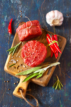 Fresh raw meat, spices and vegetables on an old blue background.