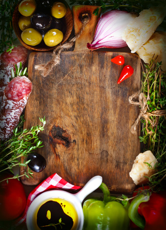 Italian food. Old cutting board  surrounded by fresh food ingredients. Toned photo.  Vintage style. photo