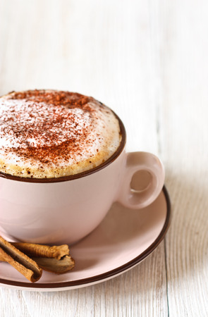 Cup of fresh cappuccino coffee and cinnamon sticks close-up.
