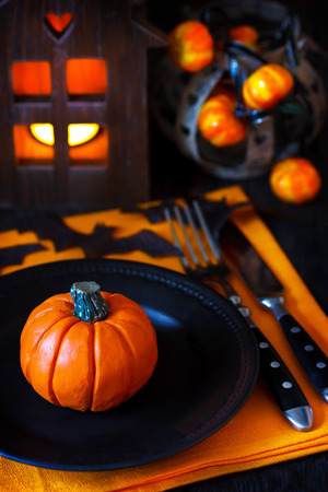 Halloween table setting with pumpkin and candle. photo