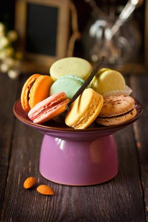 high tea: Sweet colorful macarons on a cake stand. Vintage setting.