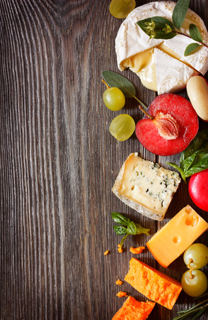 Assortment of delicious cheeses and fruit on a wooden background with copy space for text. Stock Photo