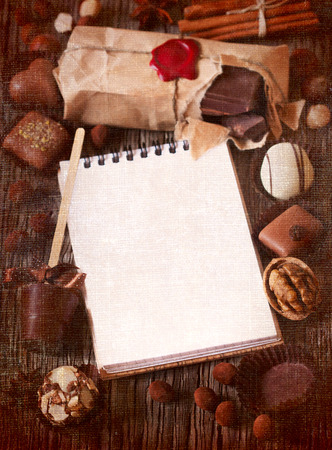Chocolate and spices frame with notebook for text on a wooden background. Textured toned photo. photo