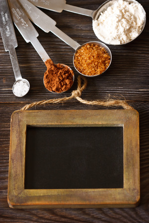 measuring spoons: Measuring spoons with cocoa, flour and brown sugar and chalk blackboard for text. Stock Photo