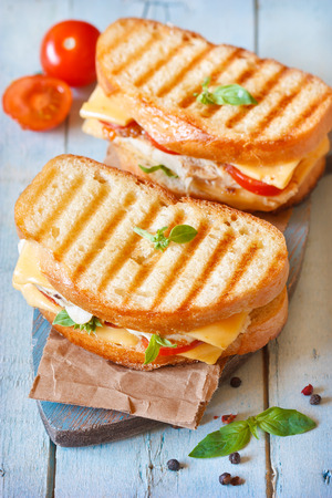 panini: Grilled cheese sandwiches with chicken and tomatoes on a rustic wooden board. Stock Photo
