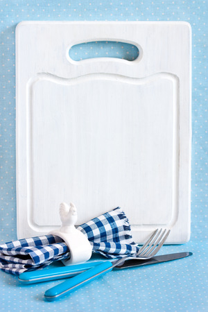 napkin ring: Old white kitchen cutting board with copy space for menu, cutlery set with fork and knife and napkin ring.