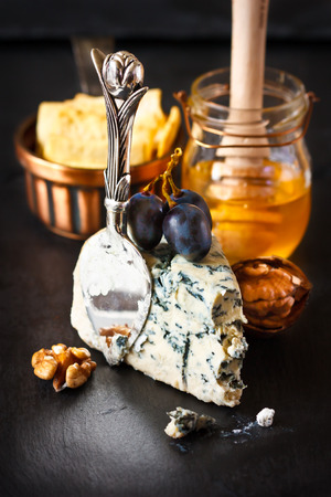 Delicious blue cheese with honey and sweet fruit on a black cooking board. photo