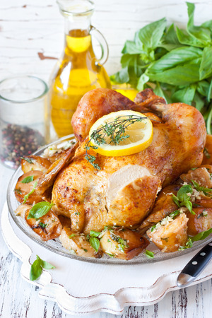 Whole roasted chicken with baked potatoes, lemon and thyme on a pan close-up. Rustic style. Stock Photo