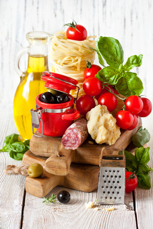 Traditional Italian food. Tagliatelle and salami with fresh tomatoes, cheese, olives and herbs. photo