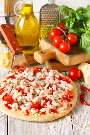 Hot shrimp pizza on a pizza maker shovel and fresh food ingredients. photo