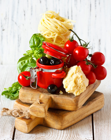 Traditional Italian food. Fresh pasta, tomatoes, cheese, olives and herbs on a wooden cooking board. photo