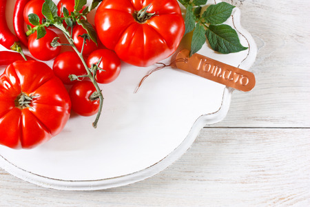 Fresh ripe tomatoes with decorative name tag on an old vintage board. photo
