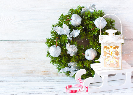 lon: Christmas wreath and candle lantern with sledge lon an old wooden background with copy space.