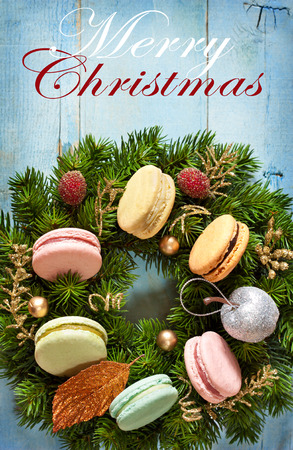 Christmas wreath with macarons cakes and decorations on an old blue wooden board. Christmas card. Vintage style. photo