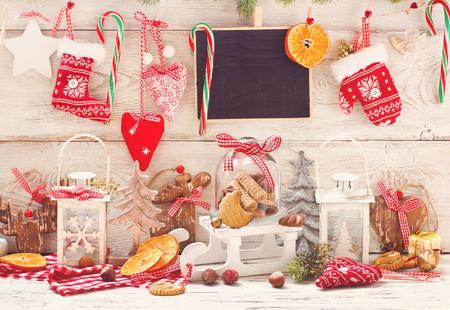 Weihnachtsschmuck mit Cookies in einer Glasglocke auf einem Schlitten mit Platz für Gruß auf Kreide Tafel. Getönten Foto.