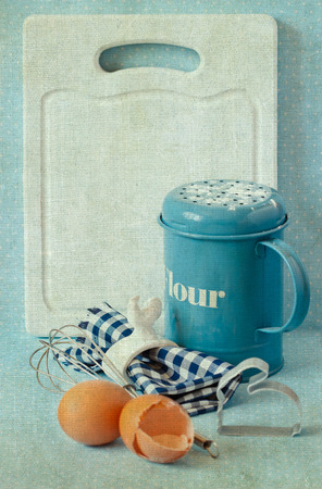 napkin ring: Old white kitchen cutting board with copy-space for writing menu, flour strainer, napkin and napkin ring, whisk and eggs. Toned photo. Vintage style.