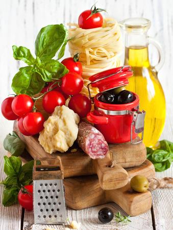 Traditionelle italienische Küche. Tagliatelle und Salami mit frischen Tomaten, Käse, Oliven und Kräutern.