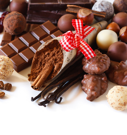 Sweet chocolates and spices on a white background. photo