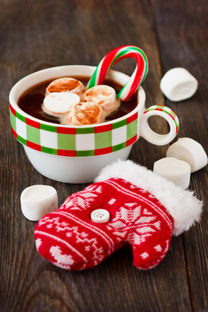 Christmas hot cocoa mix with chocolate, marshmallow and candy cane in mug. photo