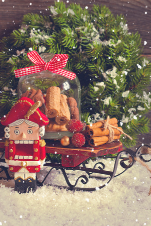 Christmas decoration with decorative nutcracker and sweet cookie in glass bell jar on a sled. Vintage style. Toned photo. photo