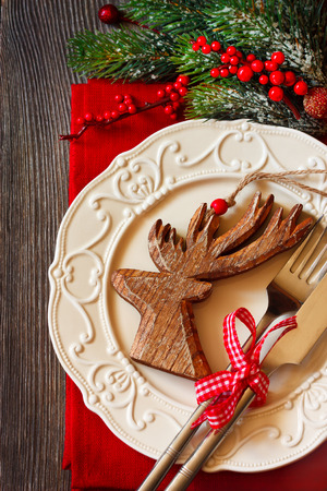 Christmas table setting with decorative wooden deer. photo