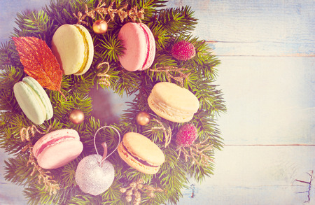 Christmas wreath with macarons cakes and decorations on an old blue wooden board. Christmas card. Vintage toned photo. photo