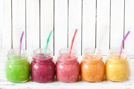 Fresh healthy smoothies with straws on a kitchen board.