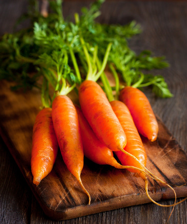 Bunch of fresh carrots on an old wooden cooking board.