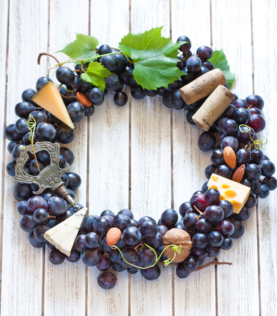wine cork: Red grape wreath decorated cheese, nuts and old corkscrew hanging on wooden board with place for text or invitation. Vintage style. Stock Photo