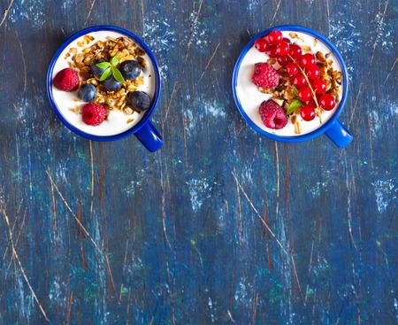 yogur: Dos tazas azules del yogur, muesli y bayas frescas para el desayuno. Concepto de alimentos saludables.