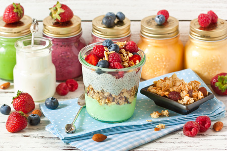 Healthy food. Fresh smoothies, glass jar of yogurt, homemade granola and breakfast with chia seeds and fresh berries. Stock Photo