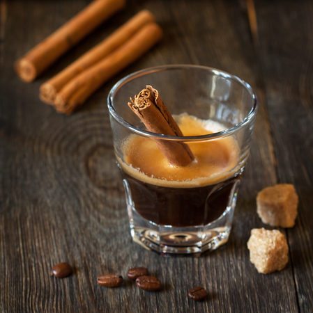 glass cup: Glass of hot cinamon espresso with coffee beans and brown sugar cubes.
