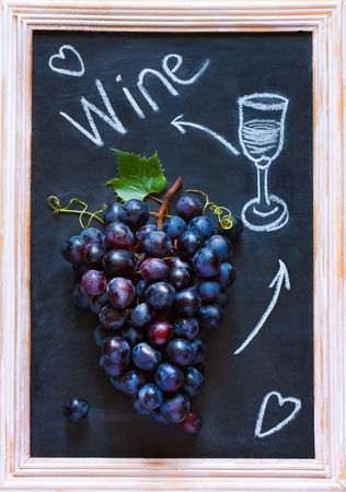 grape fruit: Fresh ripe red grape cluster on old chalk board. Invitation card.