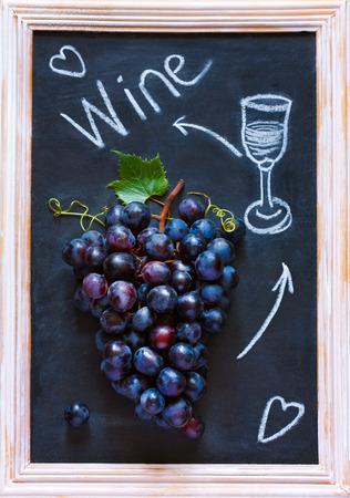 grape cluster: Fresh ripe red grape cluster on old chalk board. Invitation card.