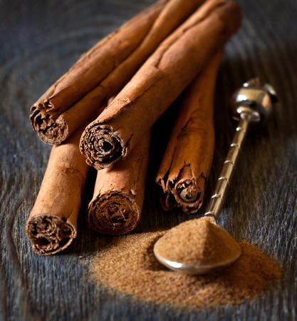 Cinnamon sticks and cinnamon powder on silver spoon close up.
