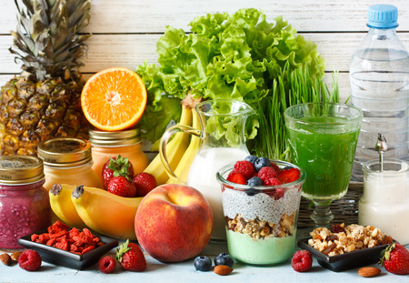 Healthy food concept. Fresh fruit and berries, granola and yogurt, smoothies and green wheat grass juice, almond milk and goji.