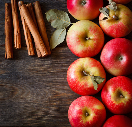 Fresh ripe red apples and cinnamon sticks on wooden background.