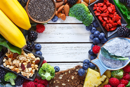 Superfood. Frame of healthy vegan ingredients on white wooden board. Healthy food concept. Stockfoto