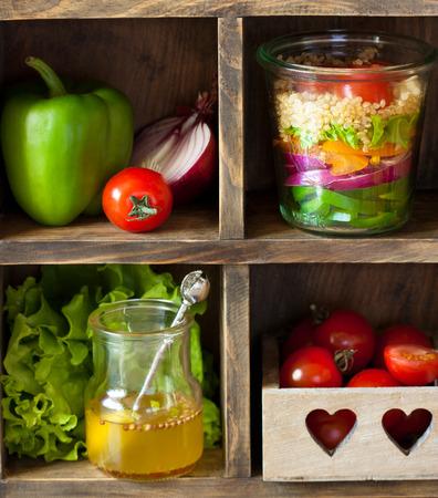 ensalada: La quinua ensalada de hortalizas y verduras frescas en los viejos estantes de la cocina de madera.