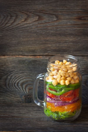 recipe background: Chick-pea vegetables salad in mason jar on wooden background.