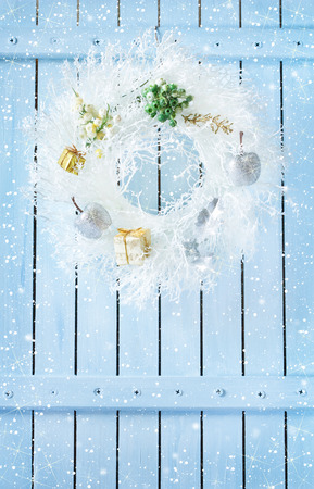 porte bois: Christmas wreath with decorations hanging on blue wooden wall with snow. Banque d'images