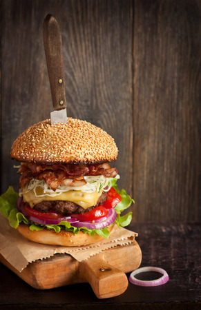 sesame seed bun: Big delicious cheeseburger stacked high with a bacon, beef patty, coleslaw, cheese, lettuce, red onion and tomato on sesame seed bun served old knife on wooden cutting board. Rustic style. Stock Photo