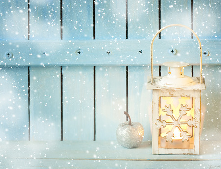 Burning christmas lantern with snow and christmas decoration on blue wooden background.