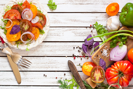 summer: Tomato salad and fresh vegetables and herbs for cooking. Stock Photo